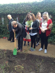 Marc Alain Grumelin, the brother of Eleonora and Roman Witonski, plants a rose with the students from Poland